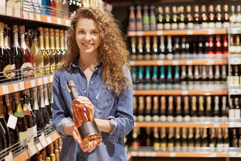 Attractive female with delighted look, holds bottle of alcoholic drink, chooses beverage in supermarket, being in good mood, likes royalty free stock images