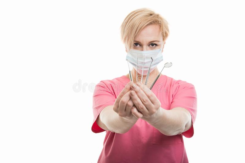 Attractive female dentist wearing scrubs showing tools royalty free stock image