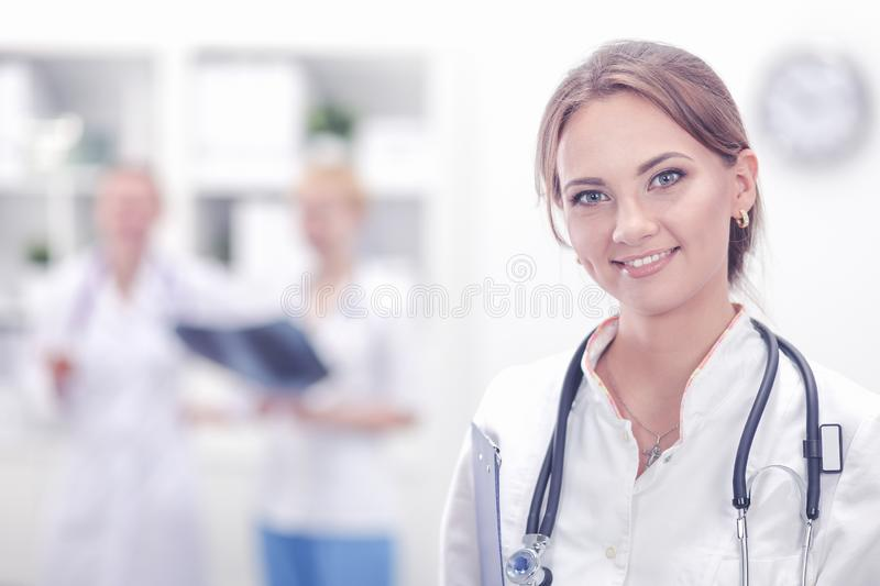 Attractive female doctor in front of medical group royalty free stock photography