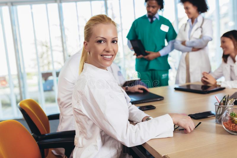 Attractive female doctor on hospital looking at camera smiling stock photo