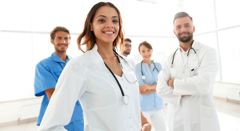 Attractive female doctor with medical stethoscope in front of medical group stock images