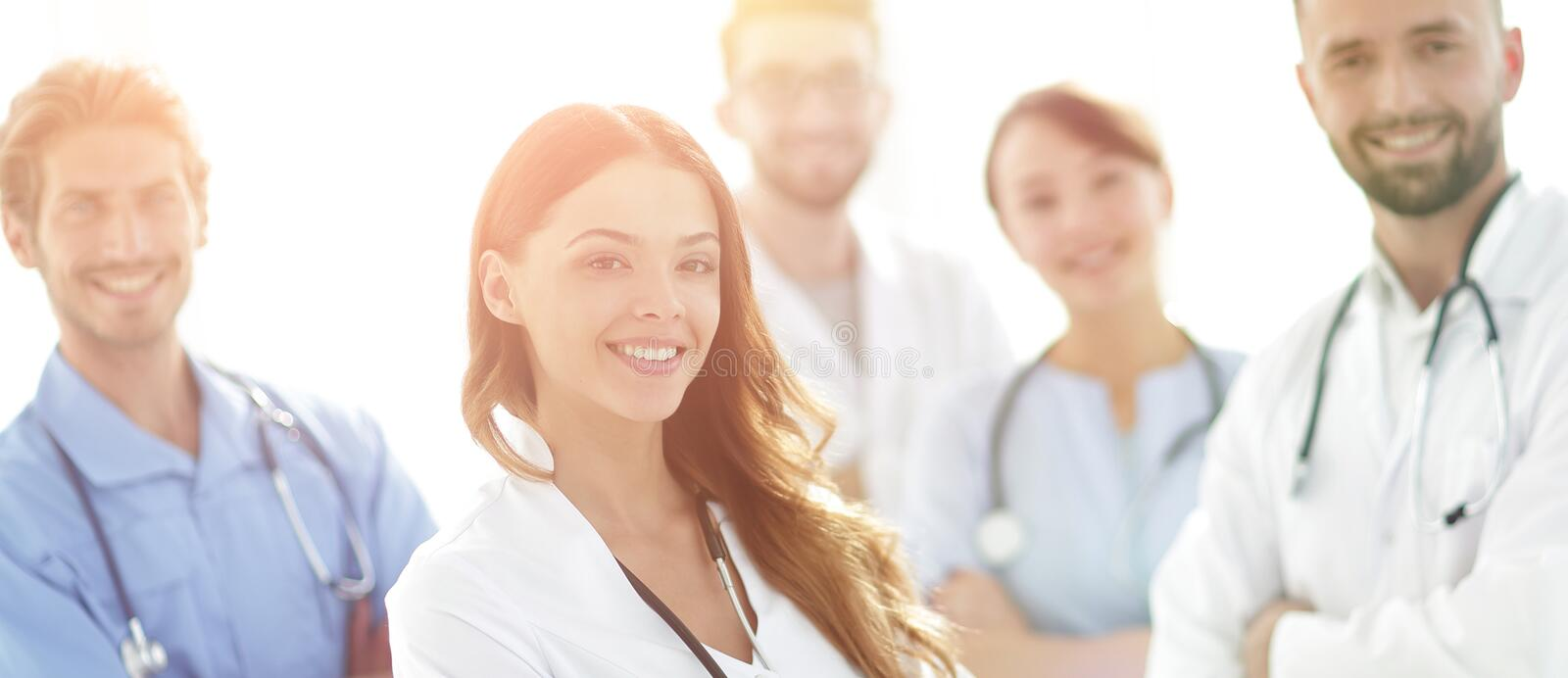 Attractive female doctor with medical stethoscope in front of medical group royalty free stock photo
