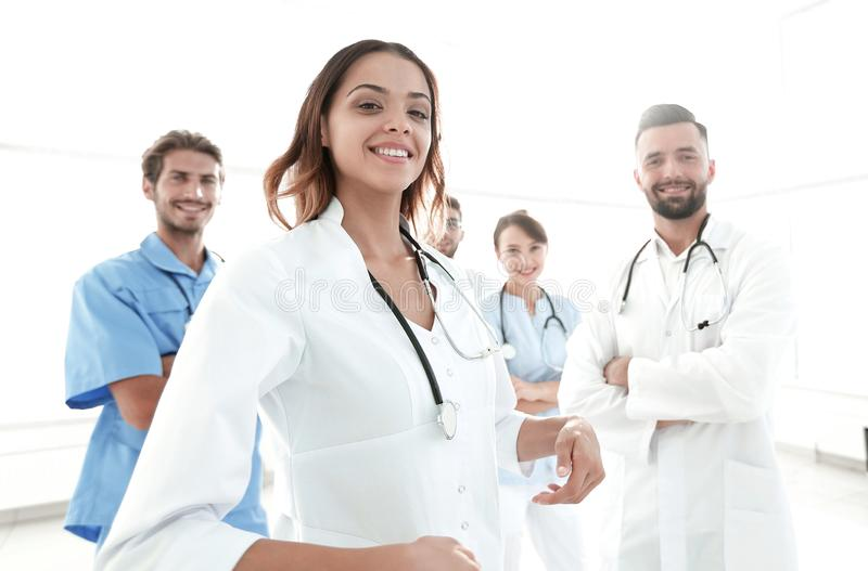 Attractive female doctor with medical stethoscope in front of medical group stock image