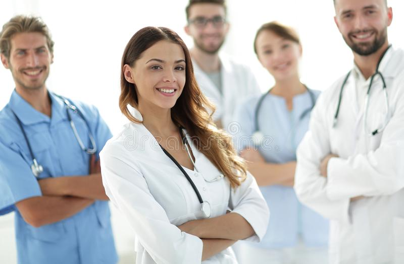 Attractive female doctor with medical stethoscope in front of medical group royalty free stock image