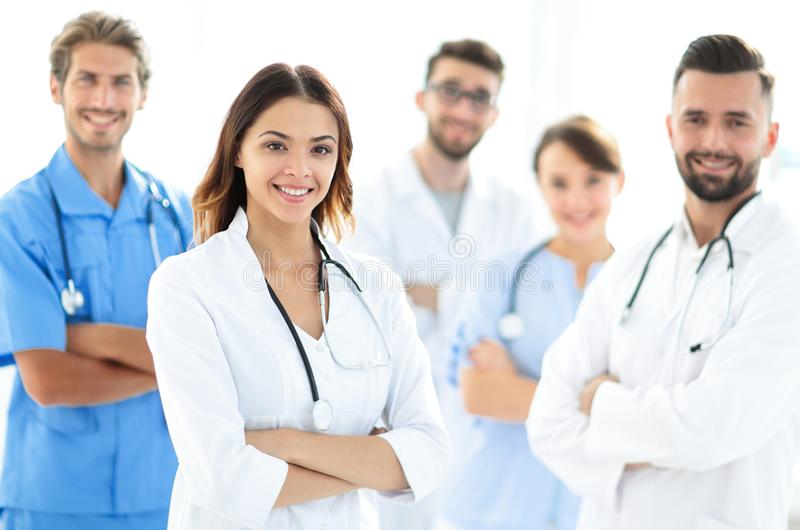Attractive female doctor with medical stethoscope in front of medical group stock photos