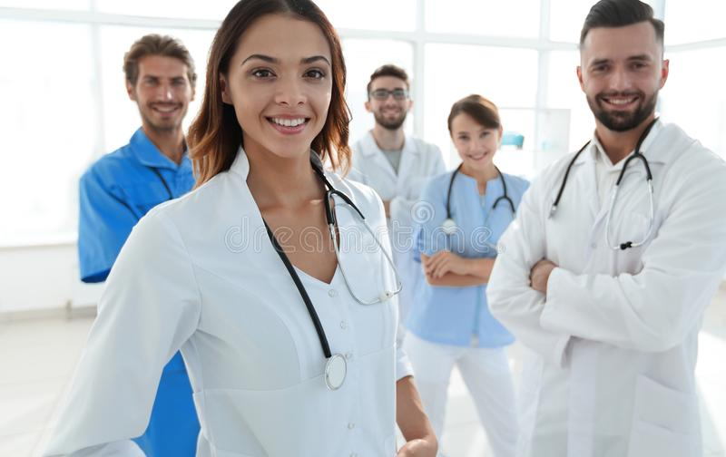 Attractive female doctor with medical stethoscope in front of medical group royalty free stock photography