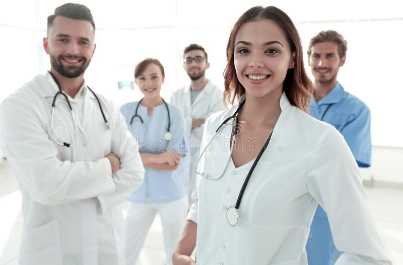 Attractive female doctor with medical stethoscope in front of medical group royalty free stock photos