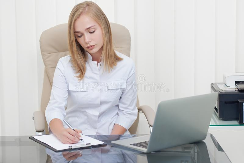 Attractive female doctor writing prescription at clinic. stock images