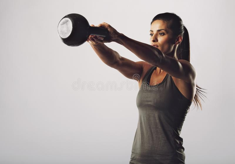Attractive female doing kettle bell exercise. Image of young attractive female doing kettle bell exercise on grey background. Fitness woman working out. Crossfit stock photo