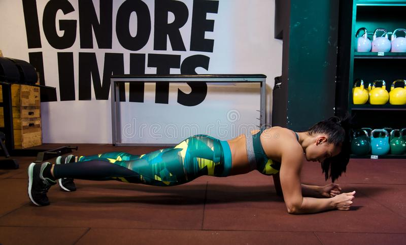Attractive female doing plank exercise in gym. Side view royalty free stock images