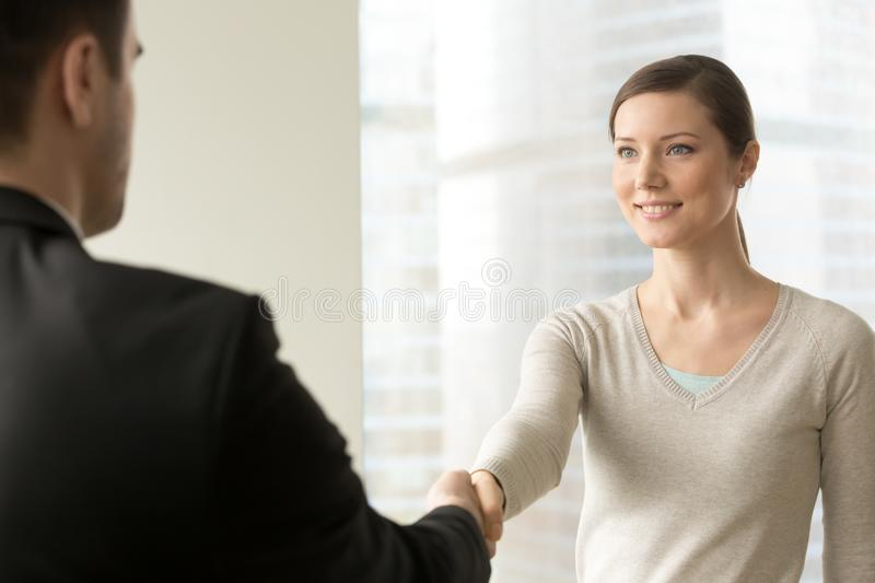 Attractive female employee handshaking with boss royalty free stock photo
