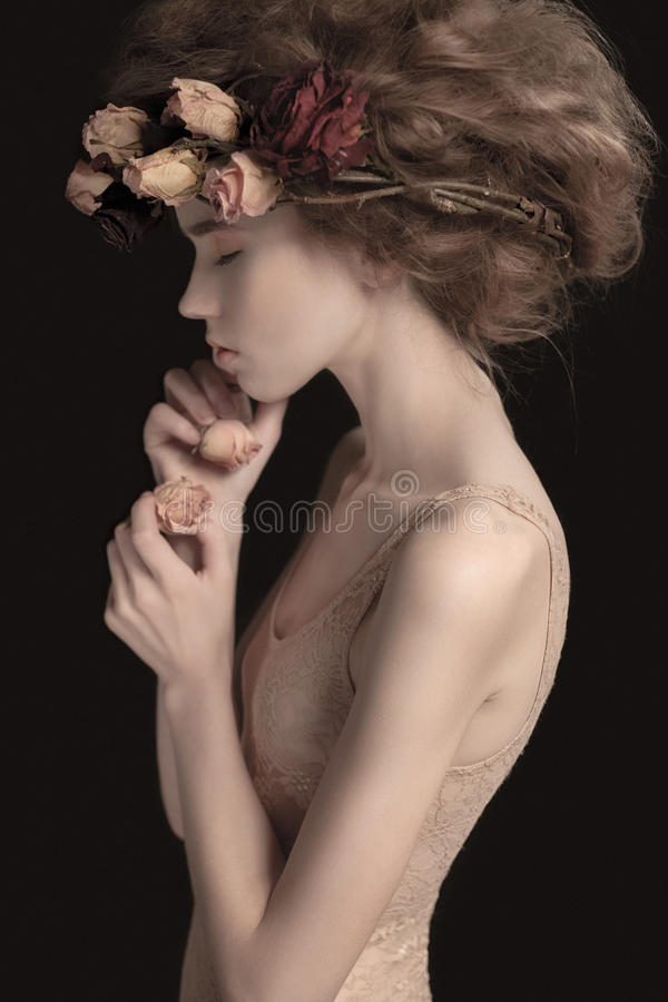 Attractive female with fashionable hairstyle. Photo of young and beautiful woman with closed eyes, fashionable hairstyle, flowers in her hair and hand near her stock photography