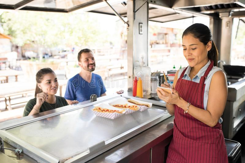 Woman taking orders in a food truck stock photos