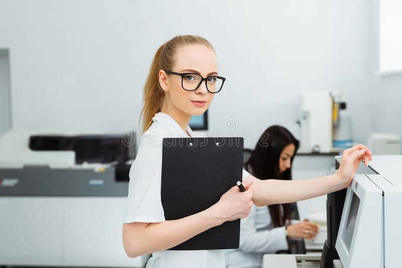 Attractive female lab worker making medical research in modern laboratory. Scientist holding documents folder with. Analysis results stock images