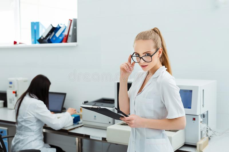 Attractive female lab worker making medical research in modern laboratory. Scientist holding documents folder with. Analysis results stock photos