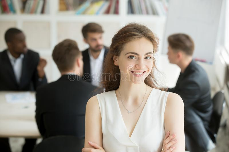 Smiling businesswoman looking at camera, team meeting at backgro royalty free stock photo