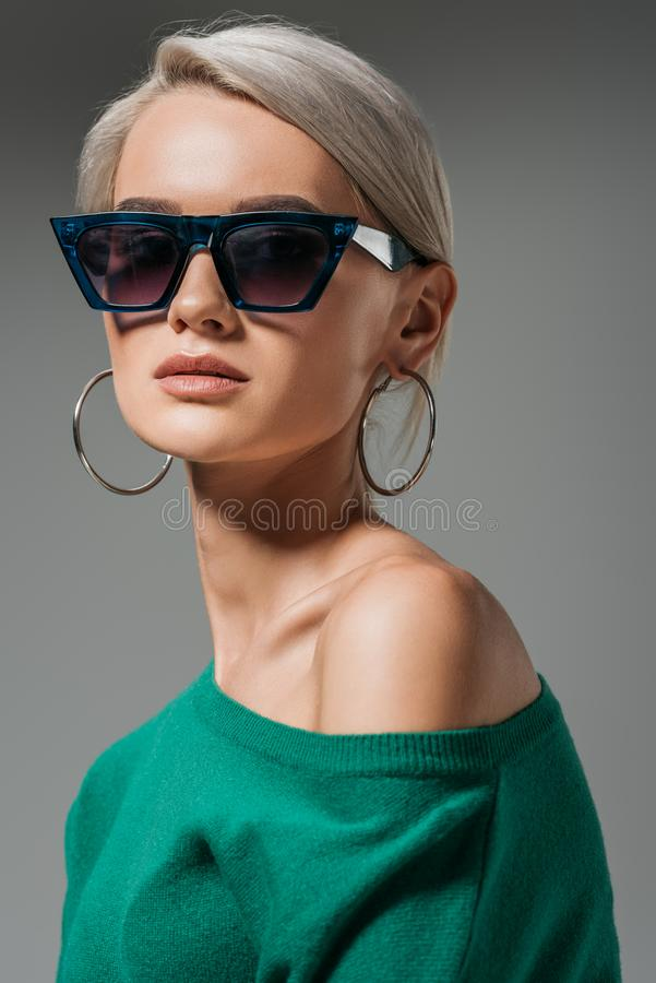 Attractive female model in sunglasses and green sweater looking at camera. Isolated on grey background stock photography