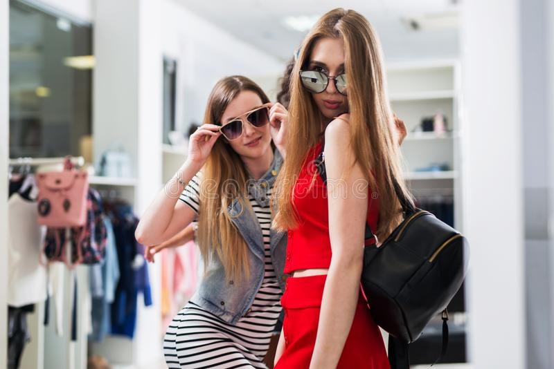 Attractive female models advertising new summer sunglasses collection in fashion store.  royalty free stock image
