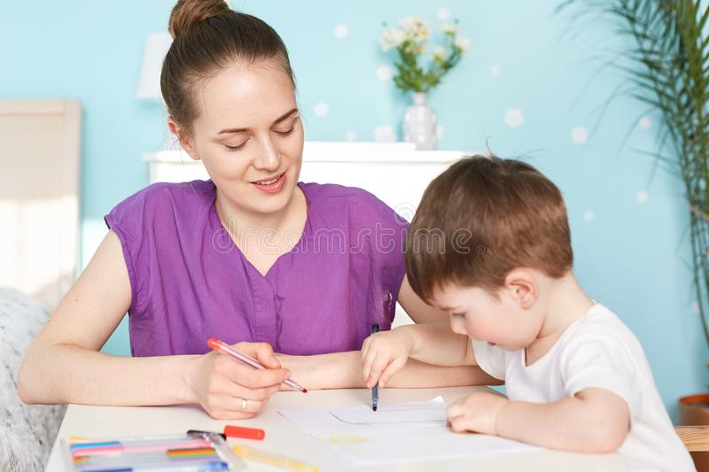 Attractive female mother sits near her little son who draws picture on blank piece of paper, being busy with creating image, use c stock photo