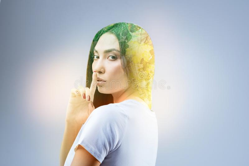 Attractive female person being nature inspired. Do not bother me. Delighted brunette turning head and raising forefinger while covering mouth stock image