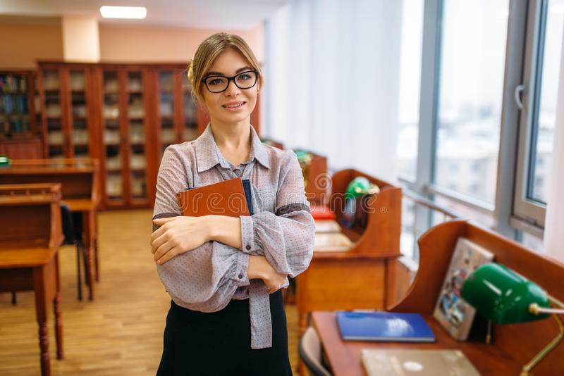 Attractive female person with books in library stock images