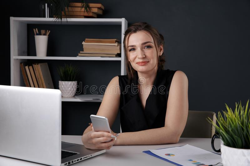 Attractive female person using phone in office sitting at the desk isolated. stock images