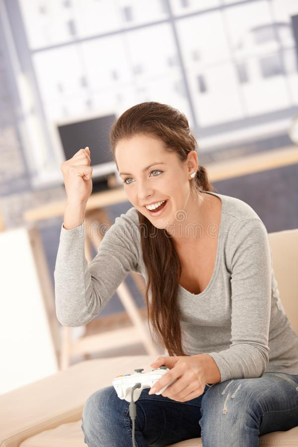 Attractive female playing video game at home. Attractive young female playing video game at home, having fun, laughing royalty free stock photography