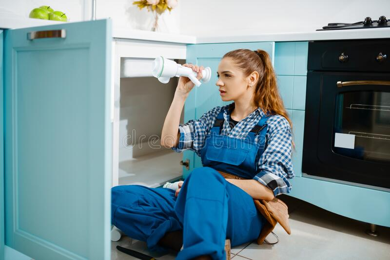 Female plumber fixing problem with drain pipe royalty free stock image