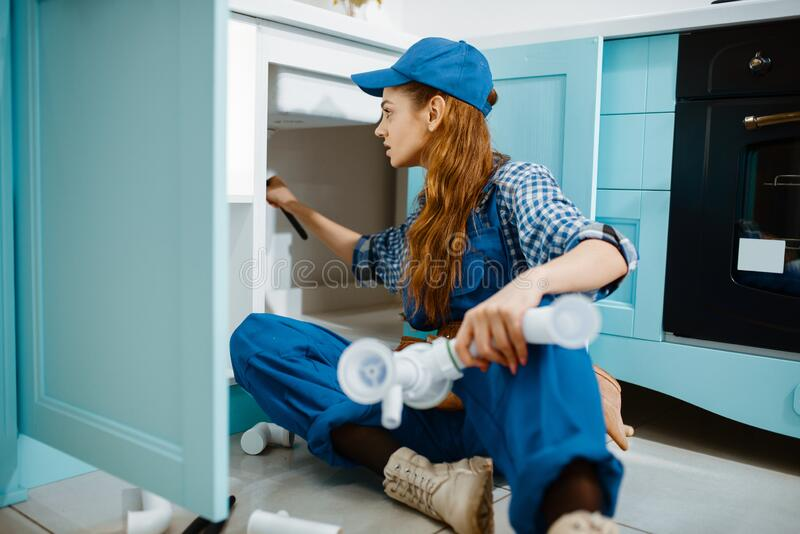 Female plumber fixing problem with drain pipe stock photo