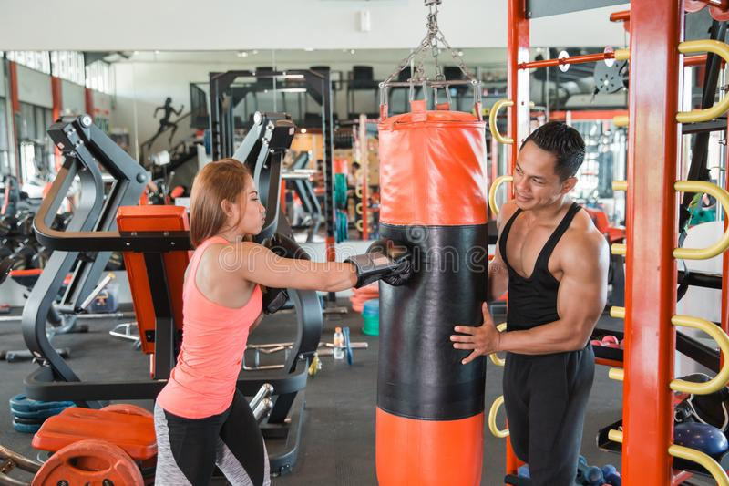 Attractive female punching a bag with trainer stock photos