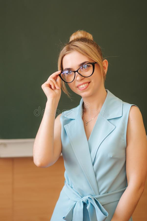 Attractive female teacher stand in front of green scholl desk stock photos