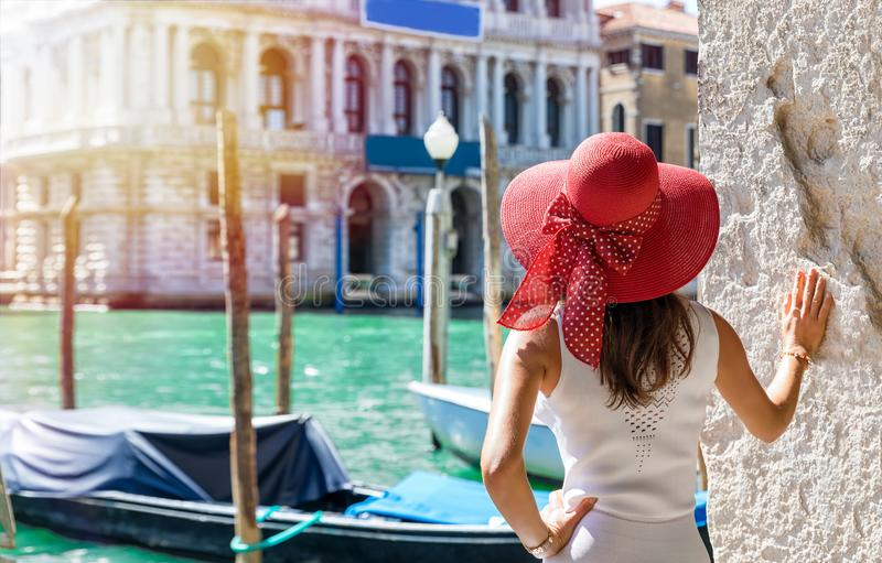 Attractive female tourist at the Canal Grande in Venice, Italy. Attractive female tourist enjoys the view to the Canal Grande in Venice, Italy, on a sunny day stock image