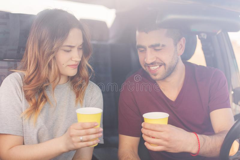 Attractive female and unshaven male couple have coffee break in auto, reach destination wih high speed. Happy family spend time stock photos