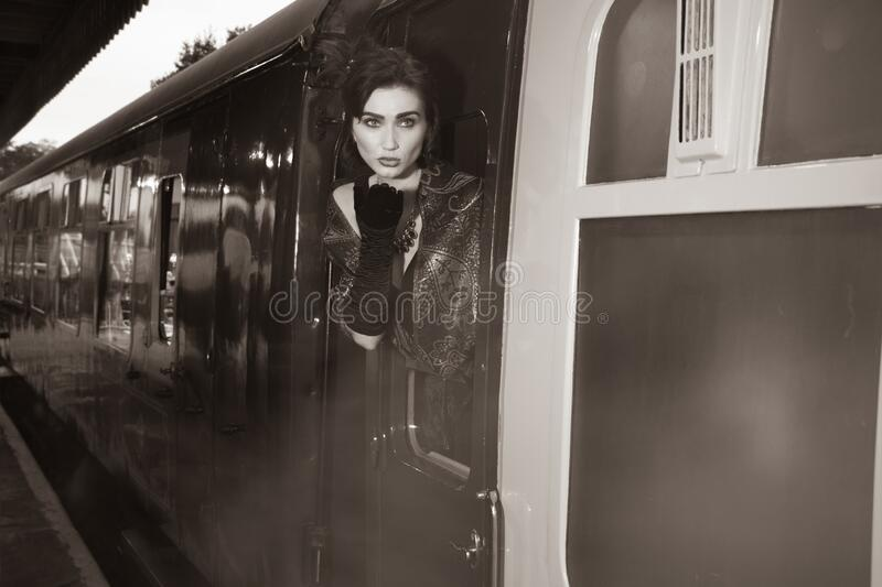 Attractive female wearing vintage evening dress leaning out of window of steam train and blowing a kiss royalty free stock images