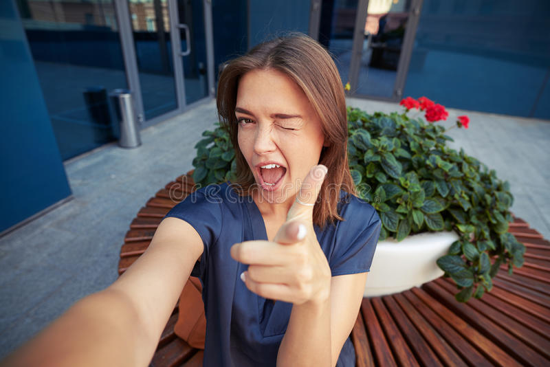 Attractive female winking at the camera while posing for a selfie. Attractive young female is winking and pointing at the camera while posing for a selfie stock images