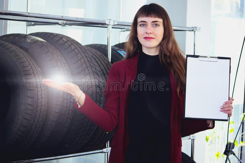 An attractive female worker sells of tires and points to clipboard royalty free stock photos