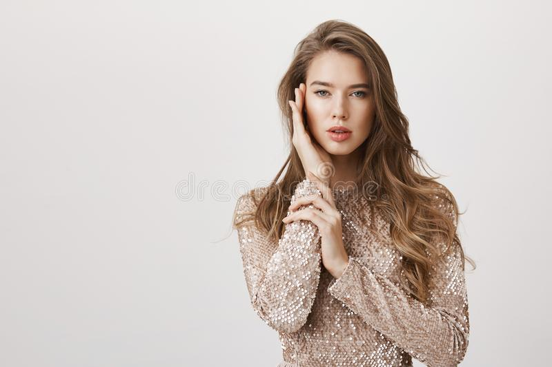 Attractive feminine woman with beautiful long hair standing in fashionable evening dress, softly touching face as if on royalty free stock images