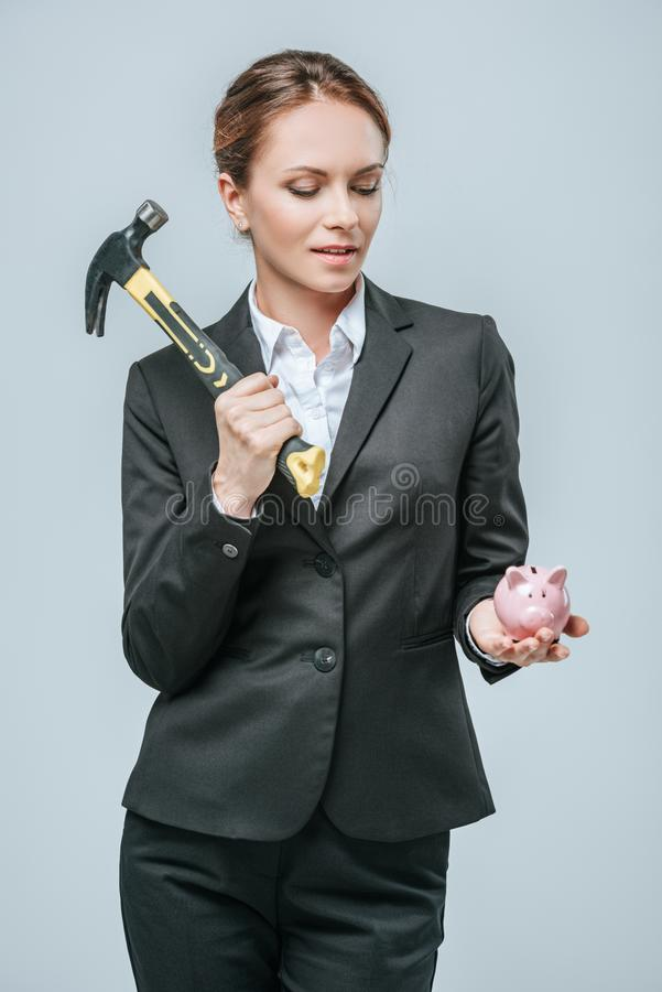 attractive financier holding hammer and piggy bank royalty free stock photography