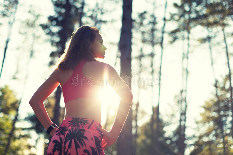 Attractive fit athletic woman in a forest, wearing smart watch, taking a break from intense workout. Sport, fitness, workout stock image