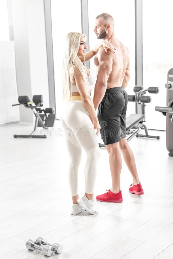 Fitness couple posing in bright gym stock photography