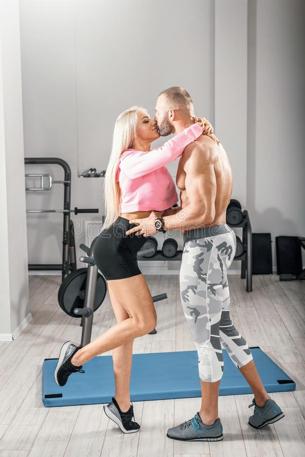 Fitness couple posing in bright gym royalty free stock photo