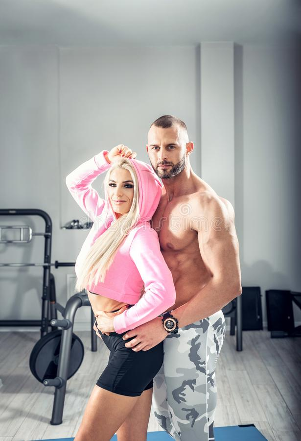 Fitness couple posing in bright gym stock photo