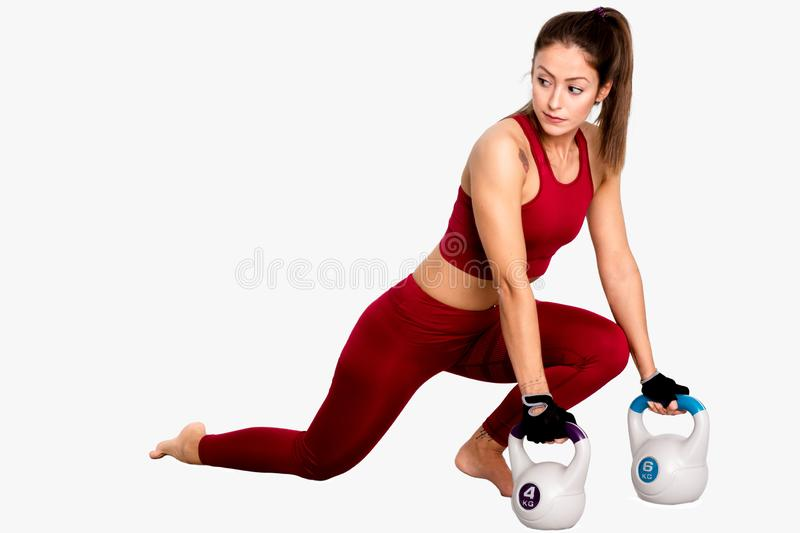 Attractive fit female doing lunge fitness exercise with grey blue kettlebell weight- Image stock photos