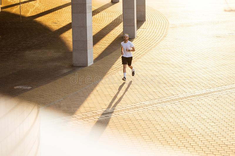 Attractive fit man running in the city at sunset. Fitness, workout, sport, lifestyle concept.  royalty free stock images