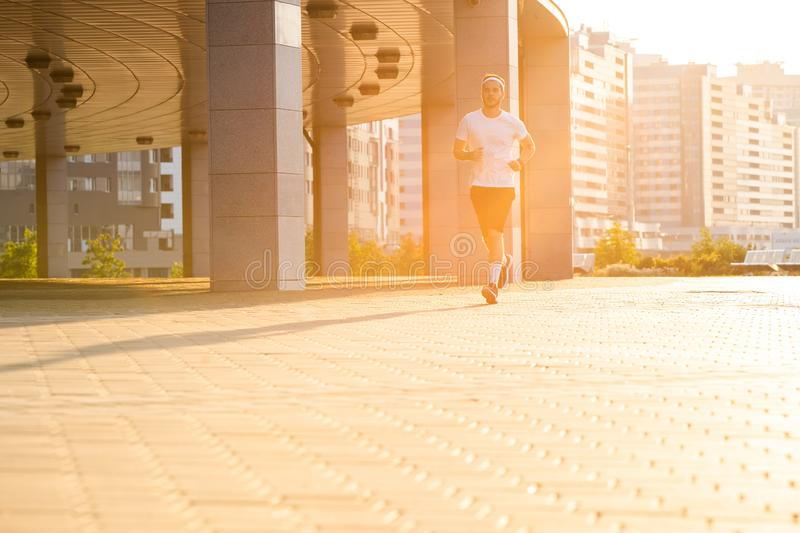 Attractive fit man running in the city at sunset. Fitness, workout, sport, lifestyle concept.  royalty free stock photography