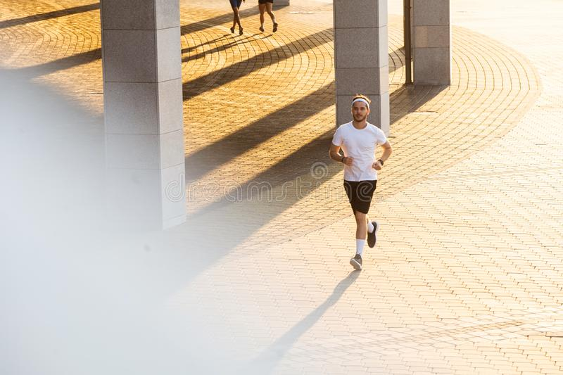 Attractive fit man running in the city at sunset. Fitness, workout, sport, lifestyle concept.  royalty free stock image