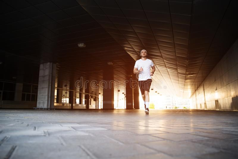 Attractive fit man running in the city at sunset. Fitness, workout, sport, lifestyle concept.  royalty free stock photo