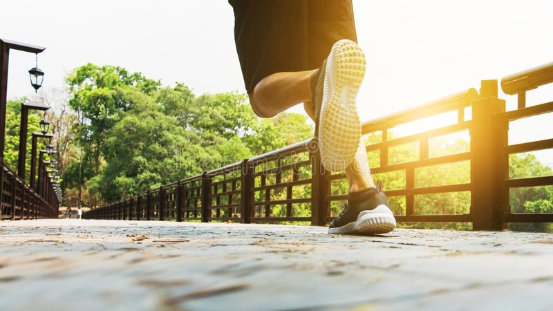 Attractive fit man running fast along bridge at a park royalty free stock photo