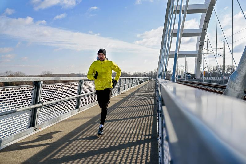 Attractive fit man running fast along modern bridge royalty free stock image