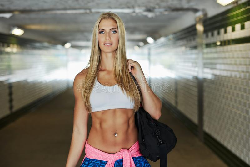 Attractive fit woman with wings of light. Attractive fit woman in sport clothing walking in a tunnel on the way to fitness training stock image